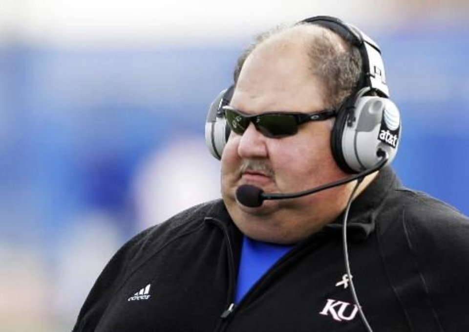 Photo - In this Oct. 24, 2009, file photo, Kansas coach  Mark  Mangino looks on during the first half of an NCAA college football game against Oklahoma in Lawrence, Kan.  Mangino has resigned two years after leading the Jayhawks to the greatest season in their checkered football history. (AP Photo/Orlin Wagner, File)