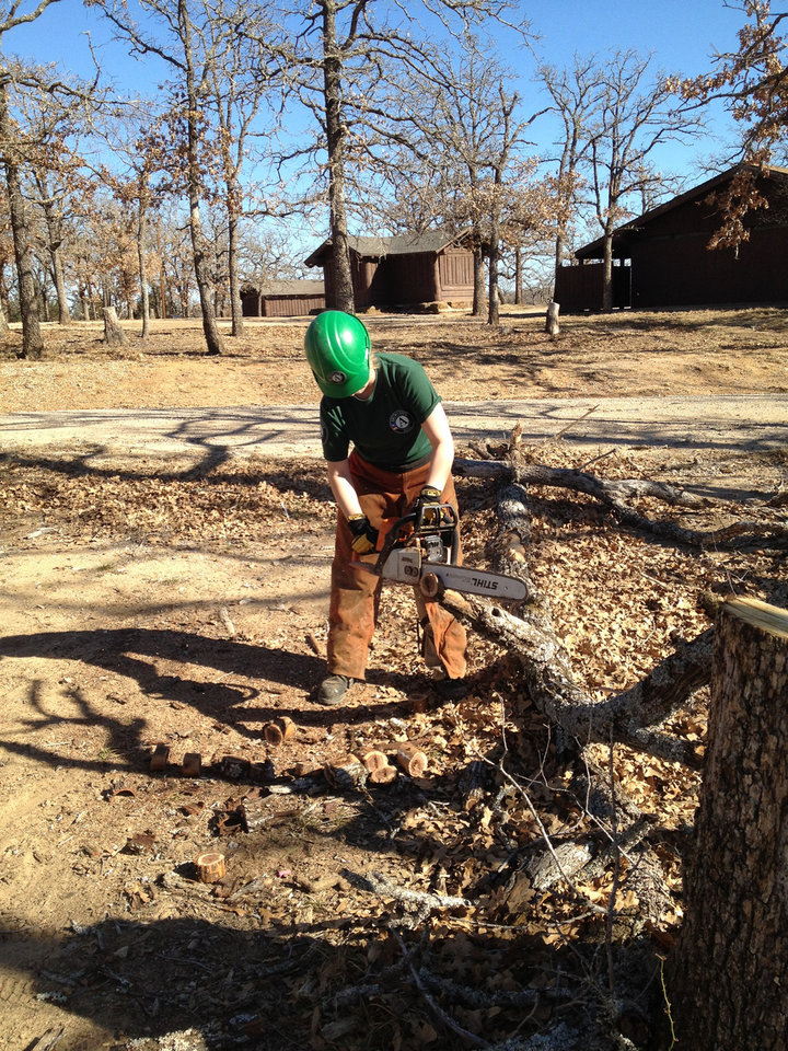 Photo - Team Leader Carol Schneider uses a chainsaw to clear branches from an area in Lake Murray State Park. PHOTO BY DANIELLE LANDRY PROVIDED.