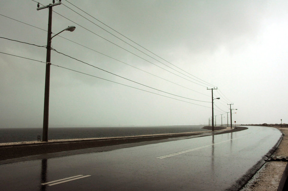 Photo -   The seaside road leading to the international airport is empty as Hurricane Sandy approaches Kingston, Jamaica, Wednesday, Oct. 24, 2012. Hurricane Sandy pounded Jamaica with heavy rain as it headed for landfall near the country's most populous city on a track that would carry it across the Caribbean island to Cuba, and a possible threat to Florida. (AP Photo/Collin Reid)
