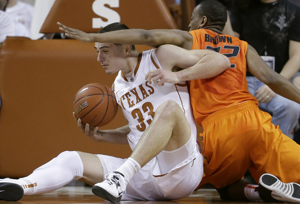 Texas' Ioannis Papapetrou (33) and Oklahoma State's Markel Brown, right, scramble for a loose ball during the first half of an NCAA college basketball game, Saturday, Feb. 9, 2013, in Austin, Texas. (AP Photo/Eric Gay) ORG XMIT: TXEG105