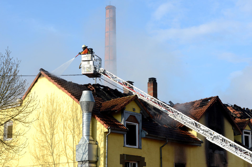 Photo - A firefighter extinguishes a fire in a house in Backnang,  Germany Sunday March 10, 2013. An early-morning fire on Sunday at the apartment building in southwestern Germany left seven people dead, six of them children, police said.  Authorities were alerted to the blaze in Backnang, a town near Stuttgart, at 4.30 a.m. Police said in a statement that they believe the fire broke out in a second-floor apartment, and said that their investigation is focusing on a heater in the apartment.  (AP Photo/dpa, Franziska Kraufmann)