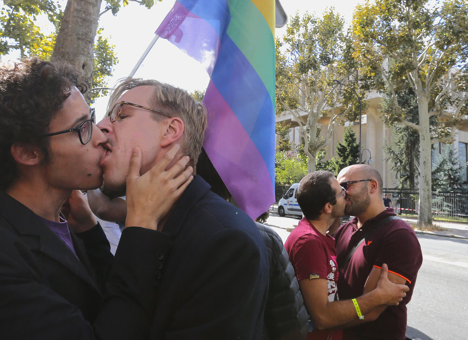 Photo - Demonstrators kiss during a demonstration in front of the Russian embassy in Paris, Sunday, Sept. 8, 2013. About a dozen gay rights supporters carried placards and chanted slogans outside the Russian embassy to protest Moscow's policies on homosexuality. (AP Photo/Jacques Brinon)