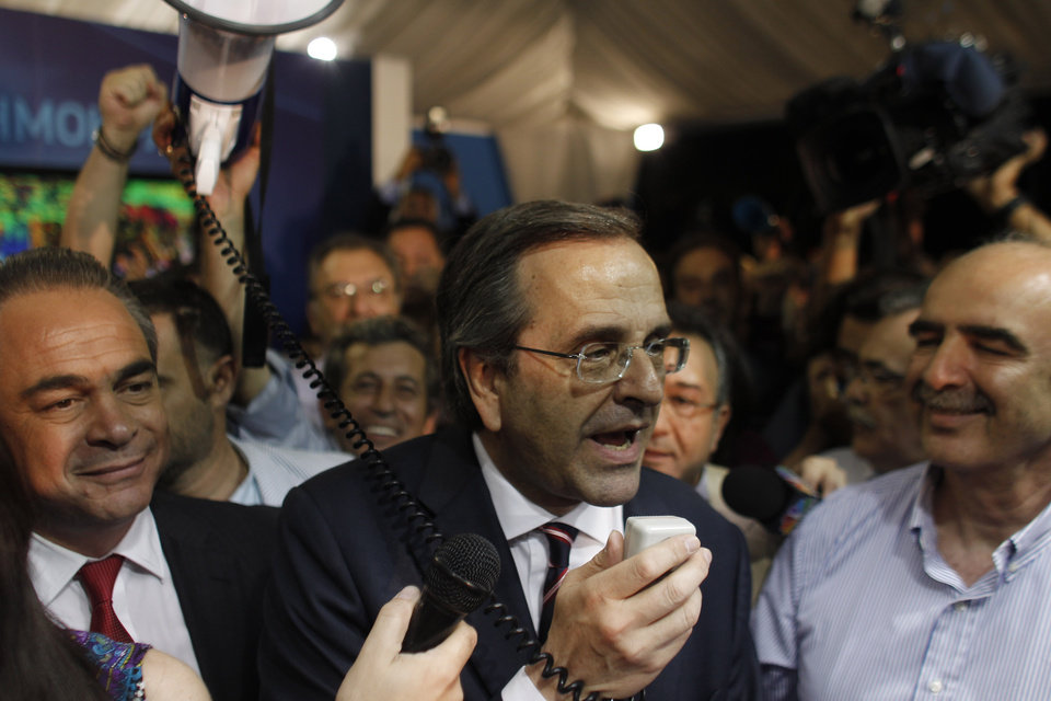 Photo -   Leader of the New Democracy conservative party Antonis Samaras, speaks to supporters at an election kiosk at Syntagma square in Athens, Sunday, June 17, 2012. The pro-bailout New Democracy party came in first Sunday in Greece's national election, and its leader has proposed forming a pro-euro coalition government.(AP Photo/Kostas Tsironis)