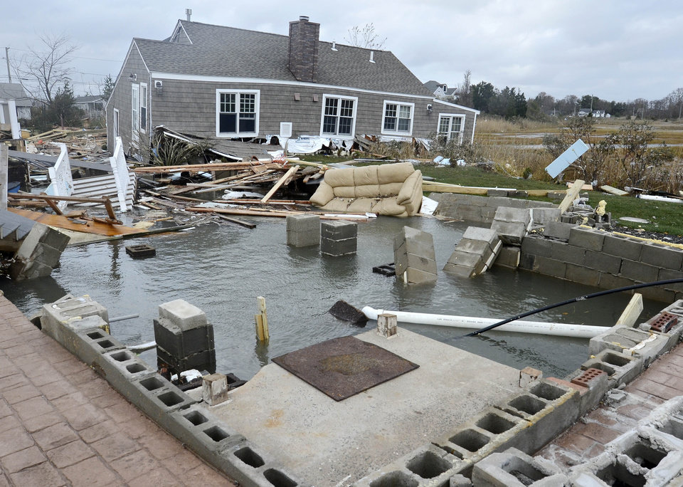 Photo - This Tuesday, Oct. 30, 2012 photo shows a house, background, pushed off its foundation, foreground, by superstorm Sandy in East Haven, Conn. (AP Photo/Jessica Hill) ORG XMIT: CTJH109