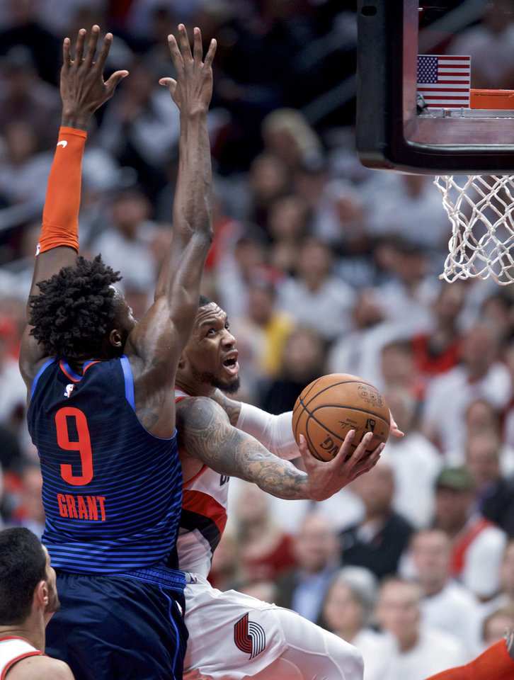 Photo - Portland Trail Blazers guard Damian Lillard, right, shoots against Oklahoma City Thunder forward Jerami Grant during the first half of Game 5 of an NBA basketball first-round playoff series, Tuesday, April 23, 2019, in Portland, Ore. (AP Photo/Craig Mitchelldyer)