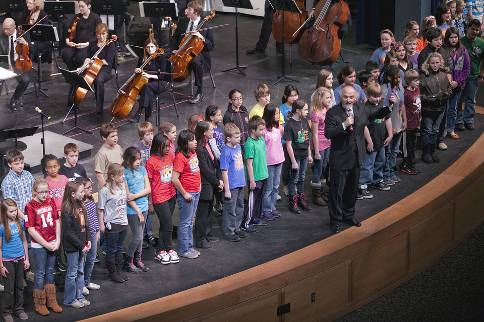 Photo - Richard Zielinski, conductor of the Norman Philharmonic, introduces the Norman School District's fifth-grade honor choir Friday in a performance of an anthem written for the city by composer Libby Larsen. PHOTO BY STEVE SISNEY, THE OKLAHOMAN