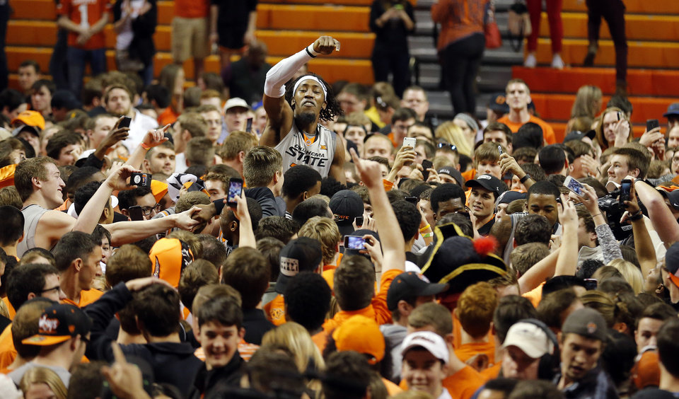 Photo - Oklahoma State's Anthony Allen Jr. (32) celebrates with fans following the men's college basketball game between Oklahoma State University and the University of Kansas at Gallagher-Iba Arena in Stillwater, Okla.,  Saturday, Feb. 7, 2015. OSU won 67-62. Photo by Sarah Phipps, The Oklahoman