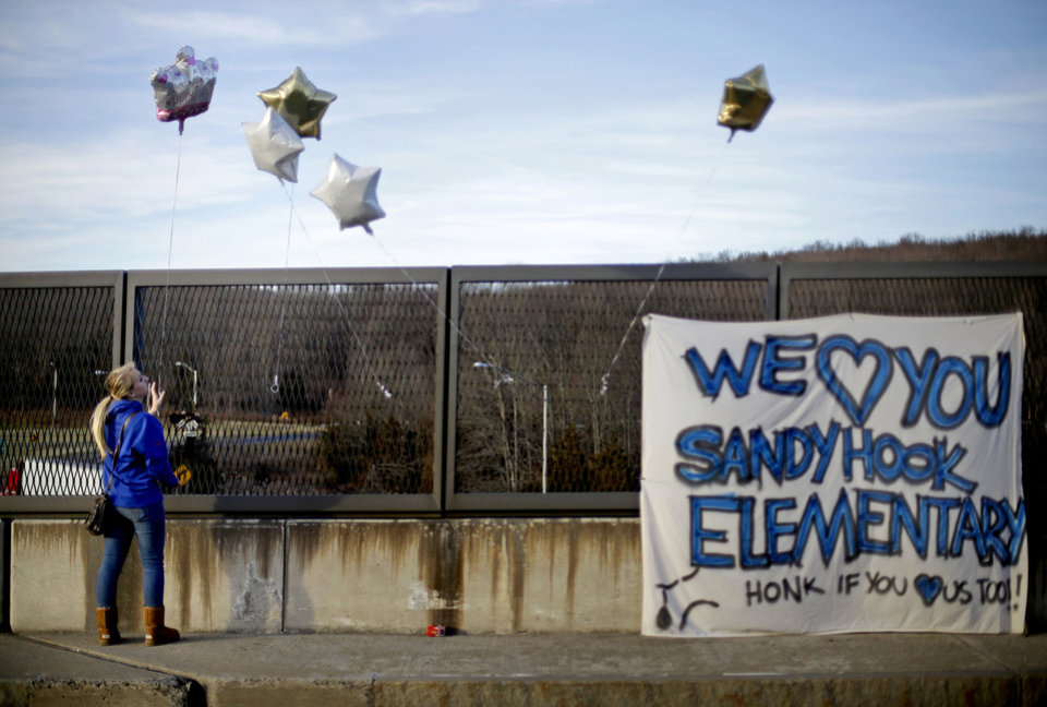 Photo - Kristin Hoyt, 18, of Danbury, Conn., ties a balloon to an overpass up the road from the Sandy Hook Elementary School, Saturday, Dec. 15, 2012, in Newtown, Conn. The massacre of 26 children and adults at Sandy Hook Elementary school elicited horror and soul-searching around the world even as it raised more basic questions about why the gunman, 20-year-old Adam Lanza, would have been driven to such a crime and how he chose his victims. (AP Photo/David Goldman) ORG XMIT: CTDG122