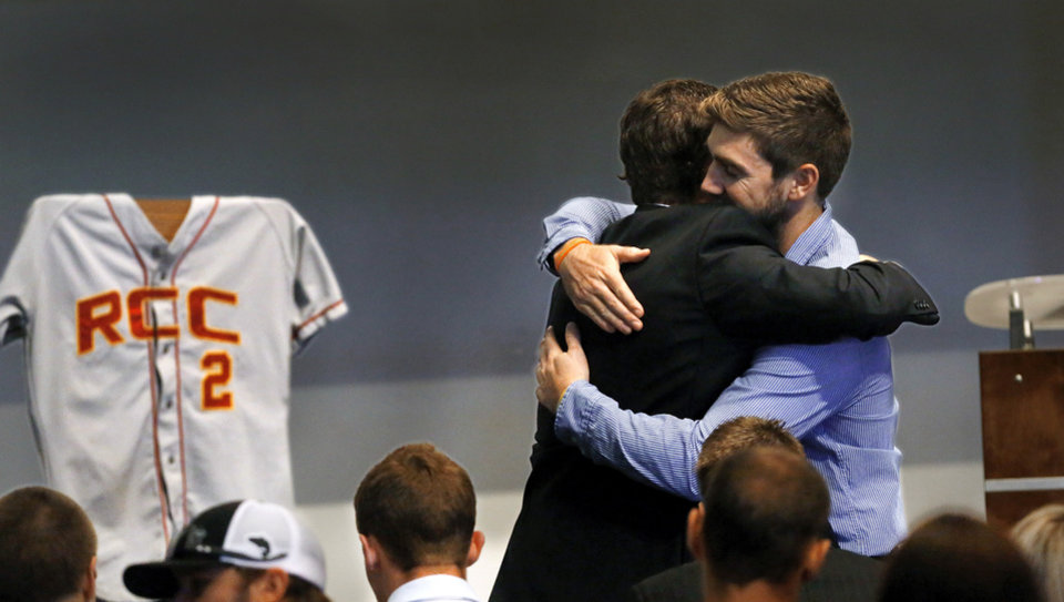 Photo - Jordan Corn, left, hugs Sam Moon before the memorial service begins. Corn and Moon, who is from Australia, were teammates of Christopher Ryan Lane when they played baseball at Redlands Community College in El Reno, Okla.  A Redlands baseball jersey with the numberLane wore while he played there was placed on the stage for the service. About 200 friends, many of them former college baseball teammates,  attended a memorial service at Oklahoma Christian University  Saturday afternoon, Aug. 24, 2013, to remember student-athlete Christopher Lane during a memorial service for the East Central University athlete who was gunned down while jogging in Duncan, Okla. last week.   Photo  by Jim Beckel, The Oklahoman.