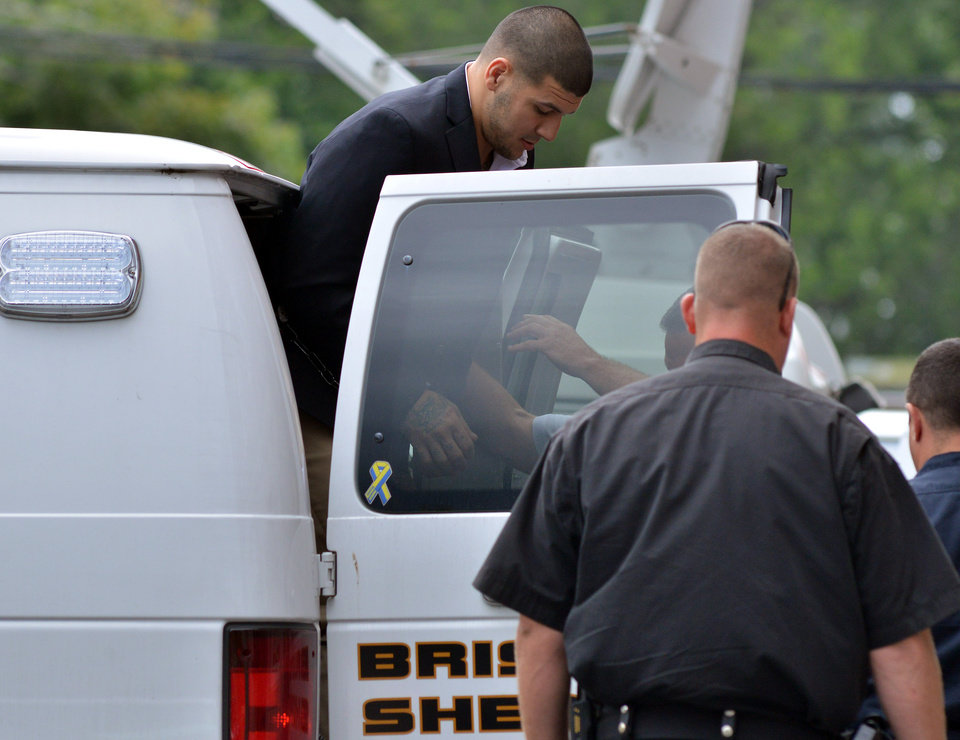 Photo - Former New England Patriot football player Aaron Hernandez, is lead from a sheriff's van into a courthouse in Attleboro, Mass., Thursday, Aug. 22, 2013. Hernandez was indicted on first-degree murder and weapons charges in the death of a friend whose bullet-riddled body was found in an industrial park about a mile from the ex-player's home. (AP Photo/Josh Reynolds)