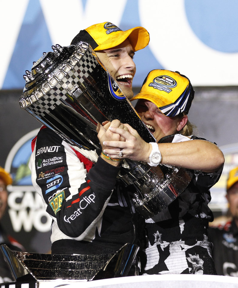 Photo -   James Buescher, left, and a team member celebrate after winning the NASCAR Nationwide Truck Series championship on Friday, Nov. 16 2012, at Homestead-Miami Speedway in Homestead, Fla. (AP Photo/Terry Renna)