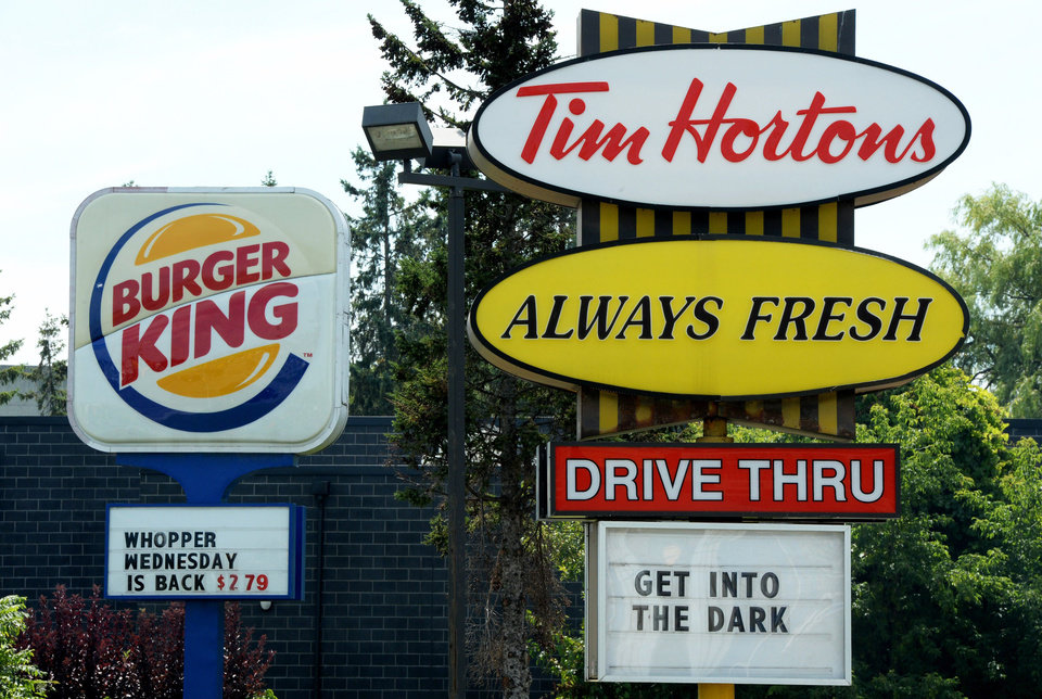 Photo - A Burger King sign and a Tim Hortons sign are displayed on St. Laurent Boulevard in Ottawa, Canada, on Monday, Aug. 25, 2014. Canada's iconic coffee chain, Tim Hortons, and Miami-based Burger King say they will join forces, but will operate as independent brands to form the world's third-largest quick service restaurant company. (AP Photo/The Canadian Press, Sean Kilpatrick)