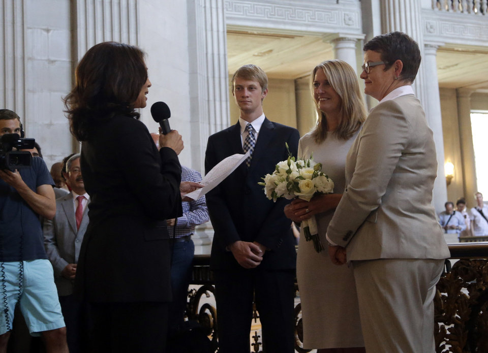 Photo - Sandy Stier, center left, and Kris Perry, at right, exchange wedding vows in front of California Attorney General Kamala Harris, left, at City Hall in San Francisco, Friday,  June 28, 2013. Stier and Perry, the lead plaintiffs in the U.S. Supreme Court case that overturned California's same-sex marriage ban, tied the knot about an hour after a federal appeals court freed same-sex couples to obtain marriage licenses for the first time in 4 1/2 years. (AP Photo/Marcio Jose Sanchez)