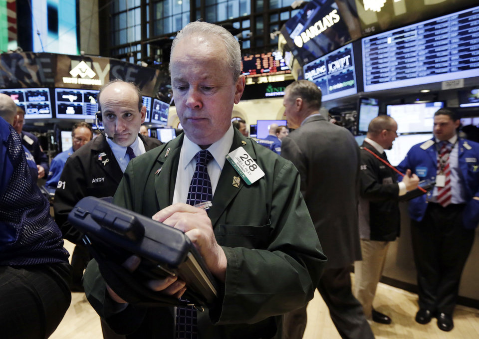 Photo - Trader James Riley, center, works on the floor of the New York Stock Exchange, Tuesday, April 8, 2014. Stocks were mixed in early trading on Tuesday after a three-day slump. Investors will start to focus on company earnings this week. (AP Photo/Richard Drew)