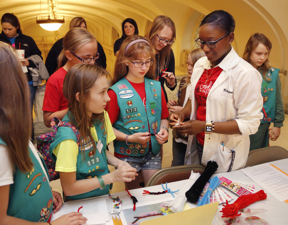 Photo -  Girl Scout STEM coordinator Sharica Robinson does a pipe-cleaner craft with Girl Scouts from Ponca City Troop 173. [Photo by Paul Hellstern, The Oklahoman]