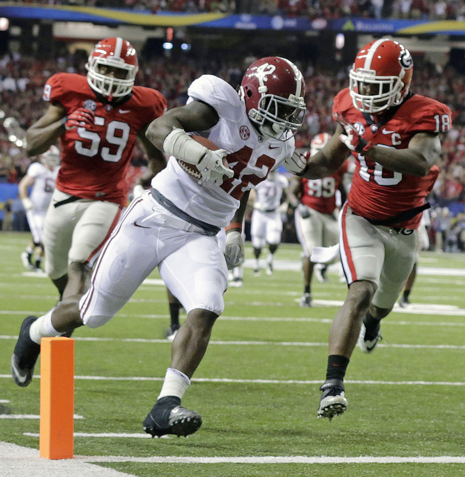 Photo - Alabama running back Eddie Lacy (42) runs into the end zone for a touchdown as Georgia safety Bacarri Rambo (18) defends during the first half of the Southeastern Conference championship NCAA college footballgame, Saturday, Dec. 1, 2012, in Atlanta. (AP Photo/Dave Martin)