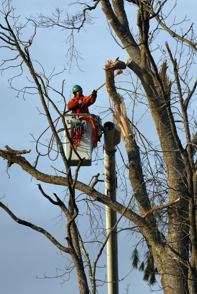 Photo - A tree service employee trims the broken branches of this tree in McNeill, Miss., Wednesday, Dec. 26, 2012. More than 25 people were injured and at least 70 homes were damaged in Mississippi by the severe storms that pushed across the South on Christmas Day, authorities said Wednesday. Hundreds of trees were damaged or destroyed, many with broken branches overhanging homes or property. (AP Photo/Rogelio V. Solis)