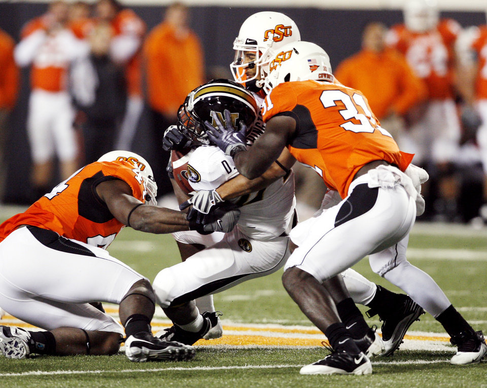 Photo - Donald Booker (44) Patrick Lavine (4) and Lucien Anoine (31) tackle Derrick Washington during the second half of the college football game between Oklahoma State University (OSU) and the University of Missouri (MU) at Boone Pickens Stadium in Stillwater, Okla. Saturday, Oct. 17, 2009.  Photo by Steve Sisney, The Oklahoman