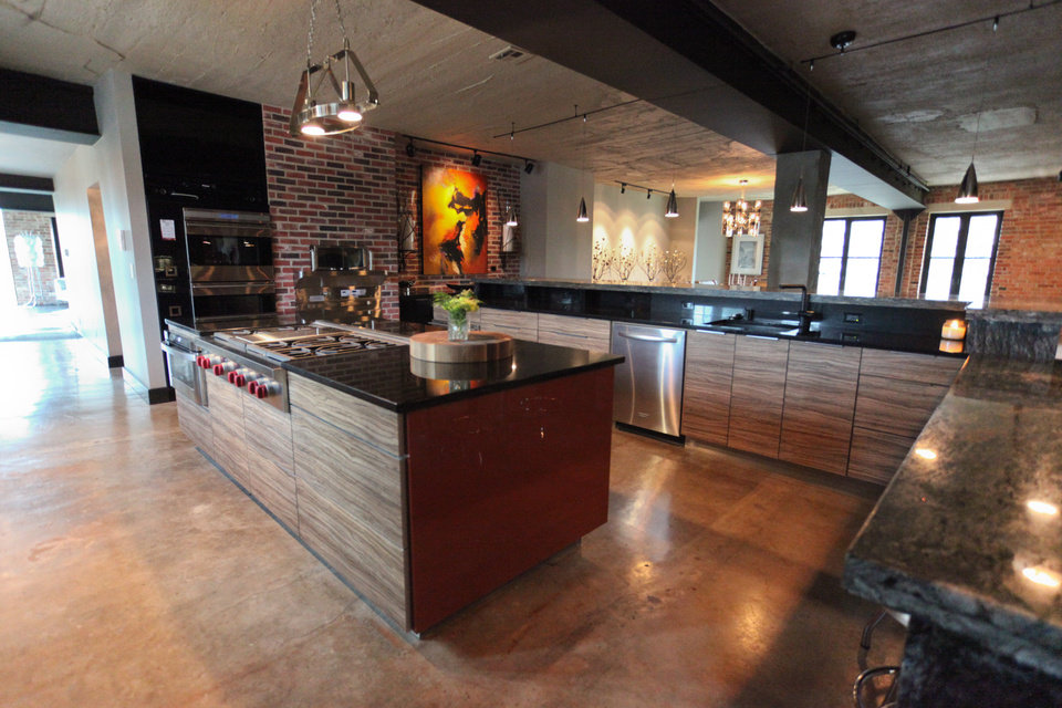 Photo -  The kitchen, featuring stone countertops combined with wood-front cabinetry and stainless steel appliances, opens into an large entertainment area. PHOTO PROVIDED