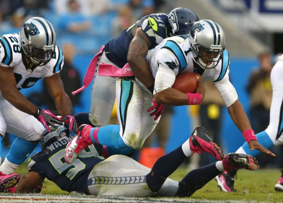 Carolina Panthers' Cam Newton (1) is tackled by Seattle Seahawks' Chris Clemons (91) and Bobby Wagner (54) during the third quarter of an NFL football game in Charlotte, N.C., Sunday, Oct. 7, 2012. (AP Photo/Bob Leverone)