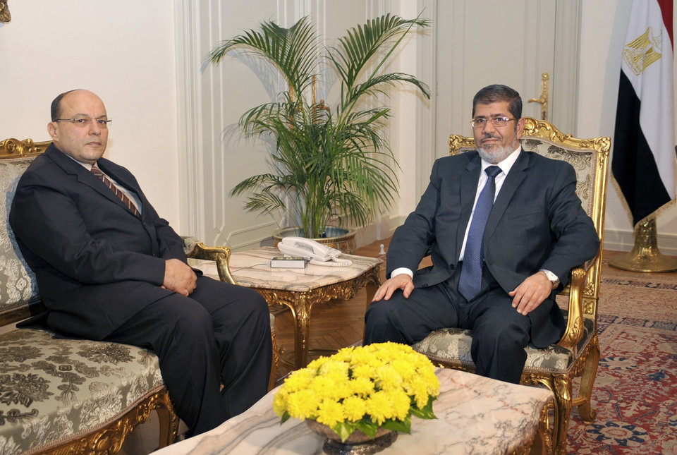 In this photo released by the Egyptian Presidency, President Mohammed Morsi, right, poses for a photograph with his new Prosecutor General, Talaat Abdullah, left, in Cairo, Egypt, Thursday, Nov. 22, 2012. Egypt\'s president on Thursday issued constitutional amendments granting himself far-reaching powers and ordering the retrial of leaders of Hosni Mubarak\'s regime for the killing of protesters in last year\'s uprising. Morsi also on Thursday fired the country\'s top prosecutor by decreeing with immediate effect that he could only stay in office for four years and replacing him with Talaat Abdullah. Morsi fired Abdel-Maguid Mahmoud for the first time in October, but had to rescind his decision when he found that the powers of his office do not empower him to do so. (AP Photo/Egyptian Presidency)