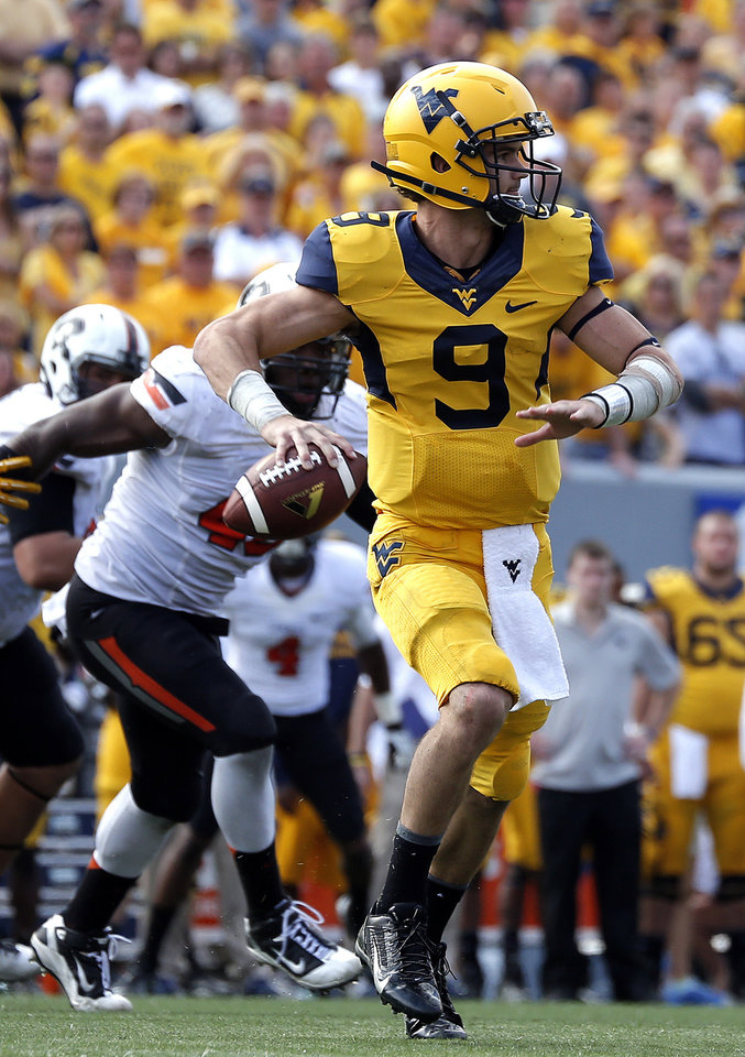 Photo - Clint Trickett (9) looks to make a throw during the second half of a college football game between the Oklahoma State University and West Virginia University on Mountaineer Field at Milan Puskar Stadium in Morgantown, W. Va.,   Saturday, Sept. 28, 2013. Photo by Sarah Phipps, The Oklahoman