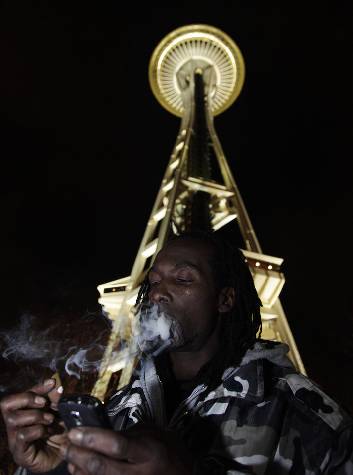 Allister Adams smokes marijuana, Thursday, Dec. 6, 2012, just after midnight at the Space Needle in Seattle. Possession of marijuana became legal in Washington state at midnight, and several hundred people gathered at the Space Needle to smoke and celebrate the occasion, even though the new law does prohibit public use of marijuana. (AP Photo/Ted S. Warren)