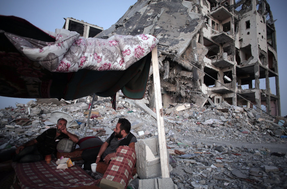 Photo - Palestinian Ziad Rizk, 38, left, sits with others in a shelter made of a blanket stretched over four boles next to one of the destroyed Nada Towers, where he lost his apartment and clothes shop, in the town of Beit Lahiya, northern Gaza Strip, Monday, Aug. 11, 2014. (AP Photo/Khalil Hamra)