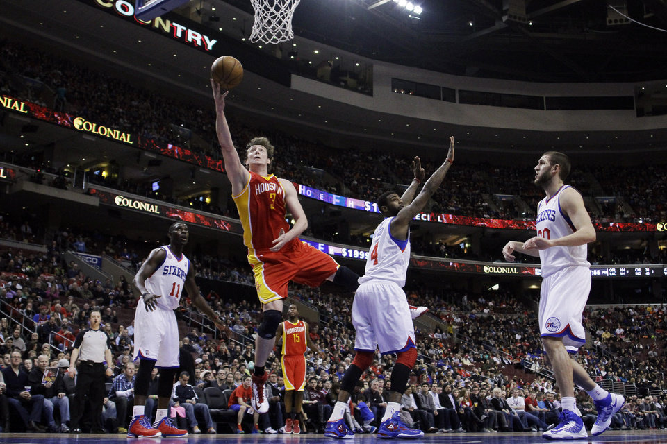 Houston Rockets\' Omer Asik (3), of Turkey, goes up for a shot past Philadelphia 76ers\' Dorell Wright (4) as Jrue Holiday (11) and Spencer Hawes (00) look on during the first half of an NBA basketball game, Saturday, Jan. 12, 2013, in Philadelphia. (AP Photo/Matt Slocum)