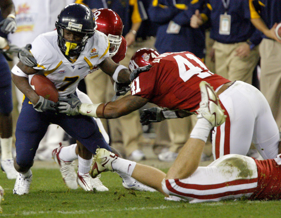 Photo - West Virginia's Noel Devine (7) gets past Oklahoma's Darien Williams (41) during the first half of the Fiesta Bowl college football game between the University of Oklahoma Sooners (OU) and the West Virginia University Mountaineers (WVU) at The University of Phoenix Stadium on Wednesday, Jan. 2, 2008, in Glendale, Ariz. 