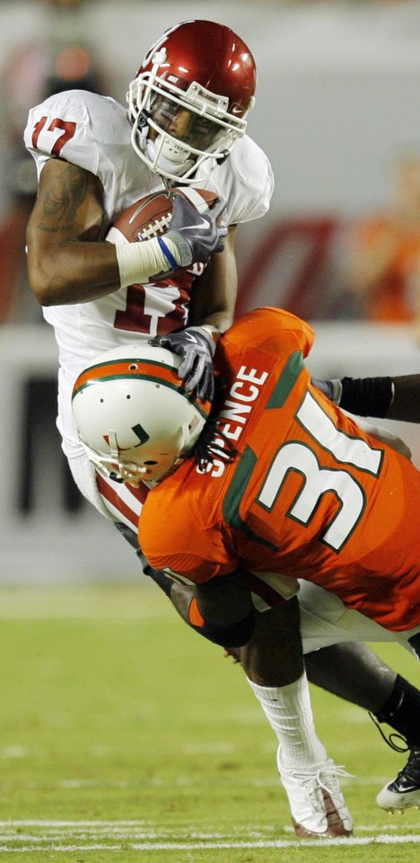 Photo - OU's Mossis Madu (17) is tackled by Miami's Sean Spence (31) after making a catch during the college football game between the University of Oklahoma (OU) Sooners and the University of Miami (UM) Hurricanes at Land Shark Stadium in Miami Gardens, Florida, Saturday, October 3, 2009. Photo by Nate Billings, The Oklahoman