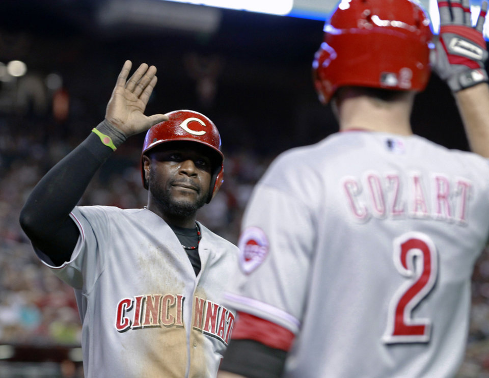 Photo - Cincinnati Reds' Brandon Phillips, left, is congratulated by Zack Cozart (2) after scoring a run against the Arizona Diamondbacks during the fourth inning of a baseball game, Saturday, May 31, 2014, in Phoenix. (AP Photo/Ralph Freso)