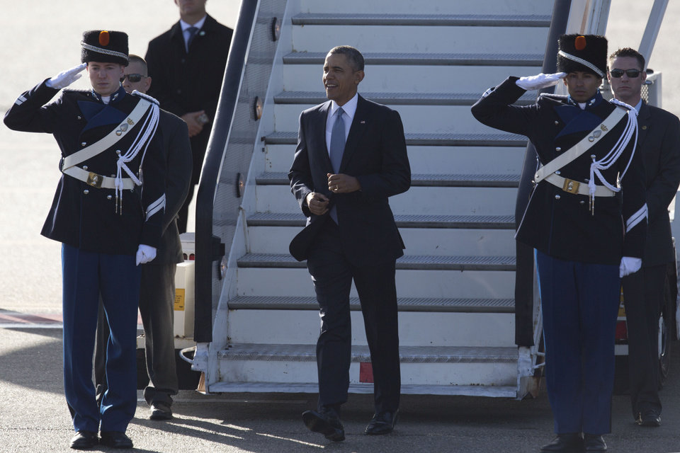 Photo - President Barack Obama walks down the stairs from Air Force One upon arrival at Schiphol Amsterdam Airport, Netherlands, Monday March 24, 2014. Obama will attend the two-day Nuclear Security Summit in The Hague. (AP Photo/Peter Dejong, POOL)