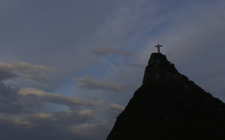Photo - Christ the Redeemer statue is silhouetted against the sky as Wednesday, July 9, 2014 dawned in Rio de Janeiro, Brazil, a day after the national soccer team's brutal and humiliating 7-1 World Cup defeat to Germany. (AP Photo/Leo Correa)
