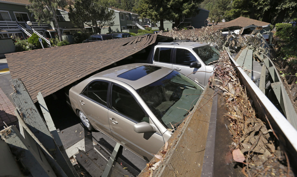 Photo - A carport is seen collapsed onto vehicles Sunday, Aug. 24, 2014, in Napa, Calif. Officials say an earthquake with a preliminary magnitude of 6.0 has been reported in California's northern San Francisco Bay area. (AP Photo/Ben Margot)