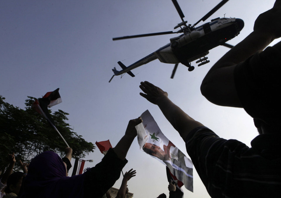 Photo - Supporters of Egyptian President-elect Abdel-Fattah el-Sissi waves his posters in front of the Supreme Constitutional Court, in Cairo, Egypt, Sunday, June 8, 2014. El-Sissi was sworn in on Sunday as president for a four-year term, taking the reins of power in a nation roiled since 2011 by deadly unrest and economic woes. (AP Photo/Amr Nabil)