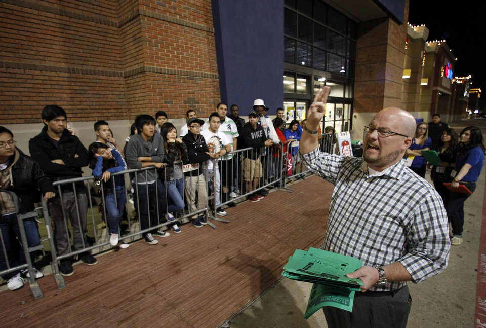 Photo -   Best Buy general manager Shaun Ogdie, right, gives instructions to shoppers before handing out sale vouchers on popular eletronics items before the store opened at midnight Thursday Nov. 22, 2012, in Arlington, Texas. (AP Photo/Tony Gutierrz)
