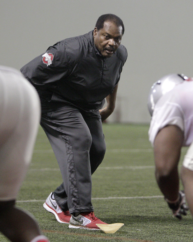 Photo - Ohio State's new assistant head coach and defensive line coach Larry Johnson works with the defensive linemen during NCAA college football practice Tuesday, March 4, 2014, in Columbus, Ohio. (AP Photo/Jay LaPrete)