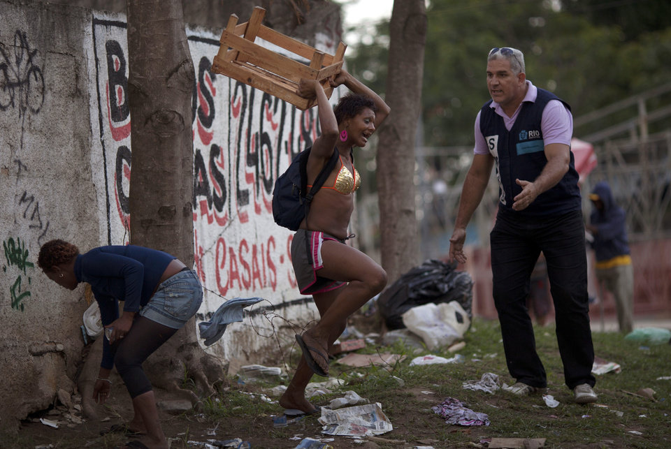 In this photo taken Nov. 22, 2012, an alleged crack addict, center, reacts as a social worker tries to calm her during a raid to take addicts to a nearby shelter in Rio de Janeiro, Brazil.  While some people go meekly, many fight, cry, scream out in desperation in their altered states. Once they're gone, their paltry belongings, ratty mattresses, pans, sweaters, are swept up by a garbage removal company. With a boom in crack use over the past decade, Brazilian authorities are struggling to help such users and stop the drug's spread, sparking a debate over the legality and efficiency of forcibly interning users. Adults can't be forced to stay in treatment, and most leave the shelters within three days. (AP Photo/Felipe Dana)