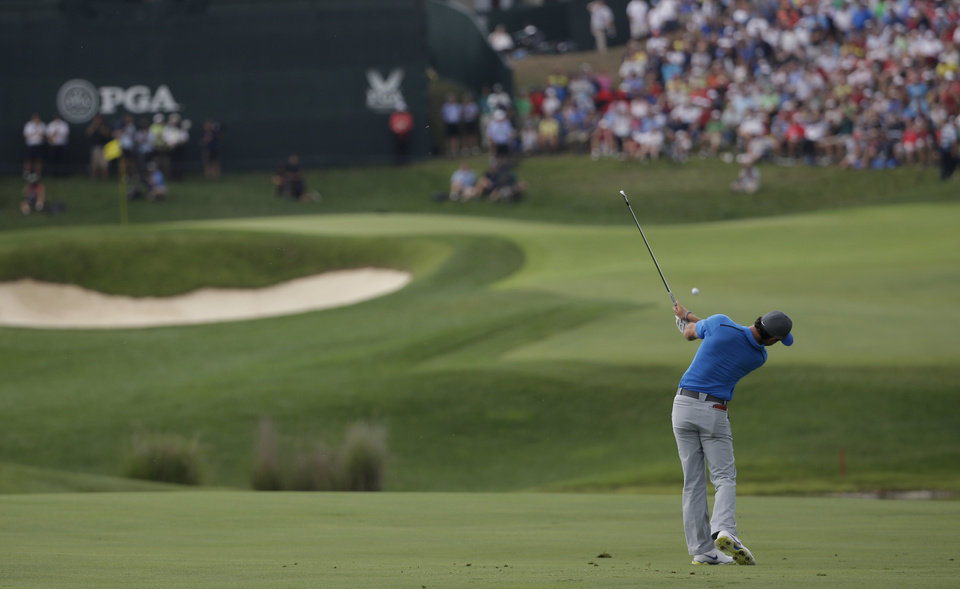 Photo - Rory McIlroy, of Northern Ireland, hits from the fairway on the 18th hole during the third round of the PGA Championship golf tournament at Valhalla Golf Club on Saturday, Aug. 9, 2014, in Louisville, Ky. (AP Photo/David J. Phillip)