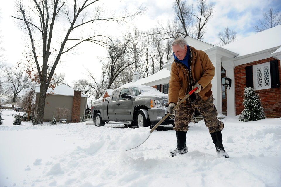 Photo - Gary McMillan, 73, of Paducah, Ky., shovels snow at his home in Paducah on Monday, March 3, 2014. A winter storm brought ice, sleet and snow to the region hampering travel and business. Area colleges, school and shopping centers have closed. (AP Photo/Stephen Lance Dennee)
