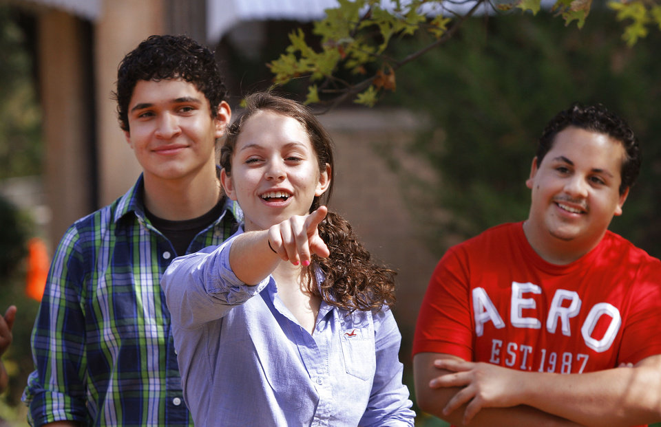 Photo - Brenda Martinez points to a teammate. Behind her are Itza Lara, left, and Juan Campos.  Participants were divided into two teams; they competed against one another to determine which team would be the first to  fully consume their allotted marshmallows. Local teens from around the metro have volunteered to be compliance checkers on local cigarette and alcohol vendors to make sure they aren't selling to underage teens. The group was honored at Eagle Ridge Institute on Aug. 25.  Photo by Jim Beckel, The Oklahoman  Jim Beckel - THE OKLAHOMAN