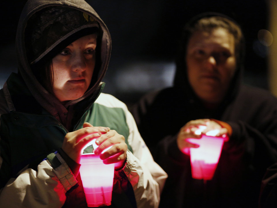 Amanda Smith holds a candle during a vigil held at Meyers lake Wednesday, Dec. 5, 2012, in Evansdale, Iowa. Hunters discovered two bodies Wednesday believed to be the young Iowa cousins who vanished five months ago while riding their bikes, authorities said. (AP Photo/Waterloo Courier, Matthew Putney)