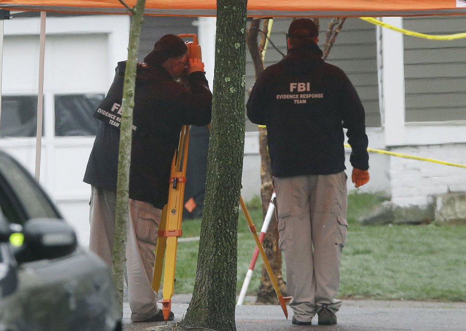 Photo - FBI agents continue to investigate the scene in Watertown, Mass. Tuesday, April 23, 2013 where Boston Marathon bombing suspect Dzhokhar Tsarnaev was captured last Friday, hiding in a backyard boat.  Tsarnaev, 19, was charged on Monday with carrying out the bombing with his older brother, Tamerlan Tsarnaev, who died last week in a gunbattle.  Tsarnaev could get the death penalty.  (AP Photo/Elise Amendola)