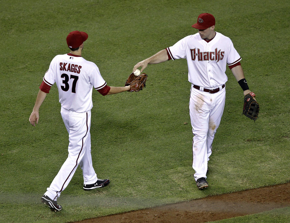 Photo -   Arizona Diamondbacks' pitcher Tyler Skaggs (37) gets the ball back from teammate John McDonald after the San Francisco Giants scored during the third inning of a baseball game on Friday, Sept. 14, 2012, in Phoenix. (AP Photo/Matt York)