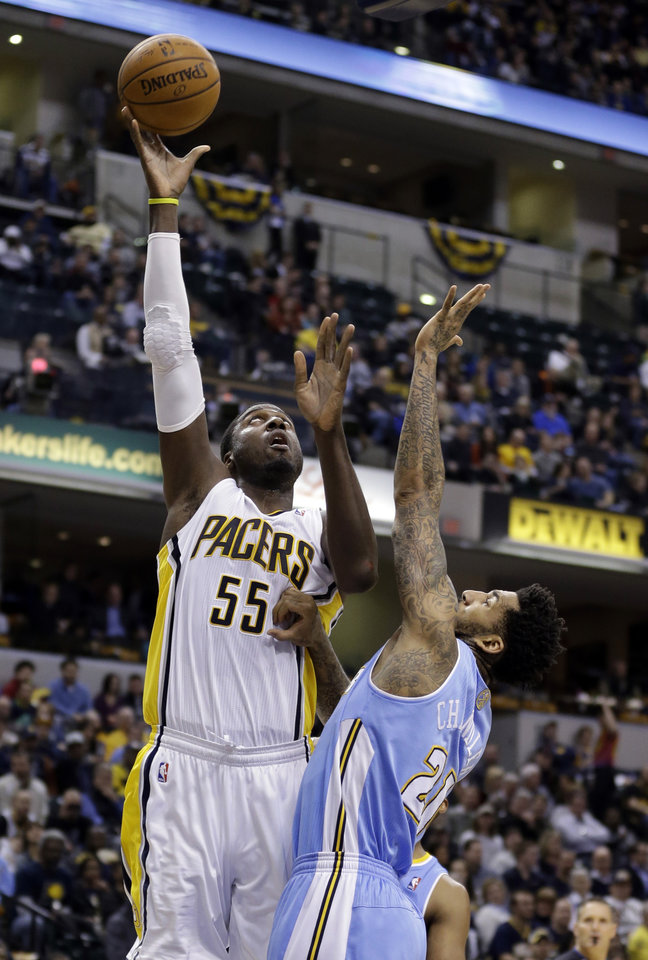Photo - Indiana Pacers center Roy Hibbert (55) shoots over Denver Nuggets forward Wilson Chandler in the second half of an NBA basketball game in Indianapolis, Monday, Feb. 10, 2014. The Pacers won 119-80.  (AP Photo/Michael Conroy)