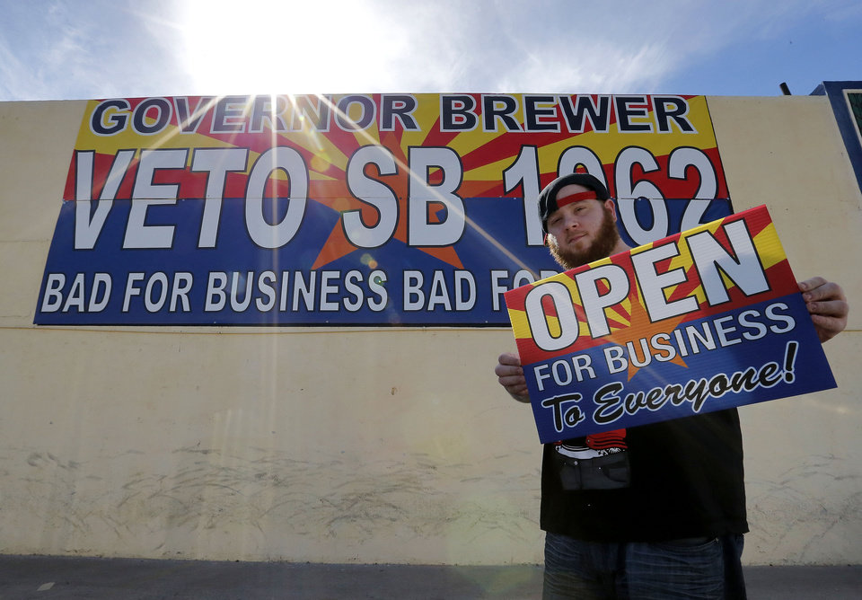 Photo - Josh Deinert, a graphic designer at Fast Signs, shows an anti-Senate Bill 1062 sign that reads