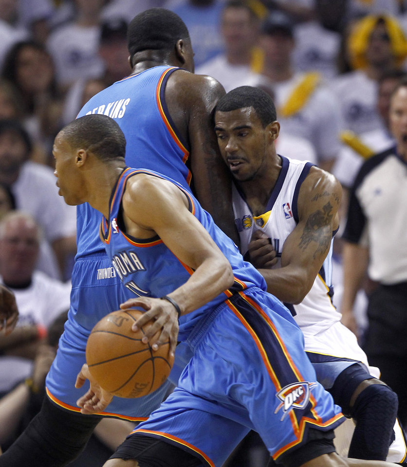 Memphis Grizzlies guard Mike Conley, right, is screened by Oklahoma City Thunder center Kendrick Perkins as guard Russell Westbrook, left, dribbles past during the first half of Game 4 of a second-round NBA basketball playoff series, Monday, May 9, 2011, in Memphis, Tenn. (AP Photo/Wade Payne)