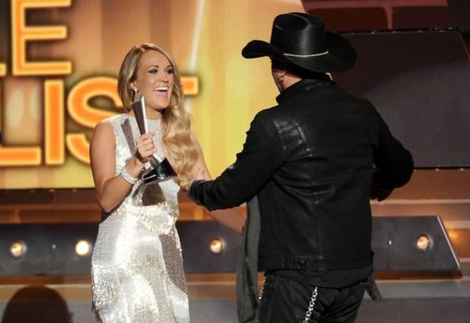 Photo -  Carrie Underwood presents the award for male vocalist of the year to Jason Aldean at the 49th annual Academy of Country Music Awards at the MGM Grand Garden Arena on Sunday, April 6, 2014, in Las Vegas. (AP)