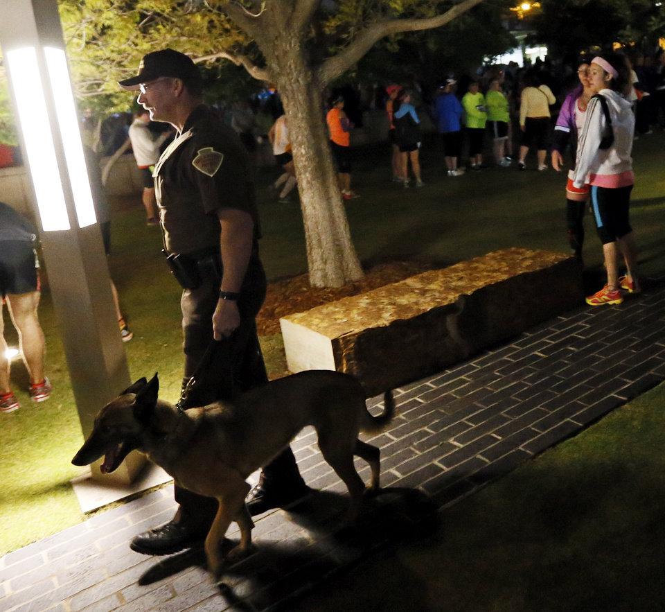 Photo - A law enforcement officer with a dog walks the grounds of the Oklahoma City National Memorial before the Oklahoma City Memorial Marathon in Oklahoma City, Sunday, April 28, 2013. Photo by Nate Billings, The Oklahoman